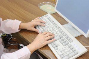 パソコンを打つ白衣の女性