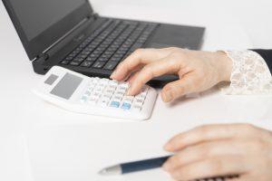 電卓で計算をする女性
