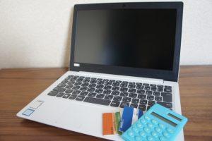 パソコンと通帳と電卓