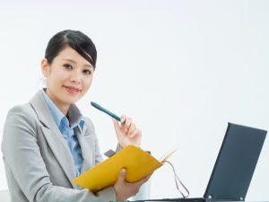 手帳を手に仕事中の女性