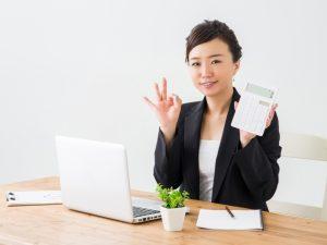 電卓を手に説明する女性